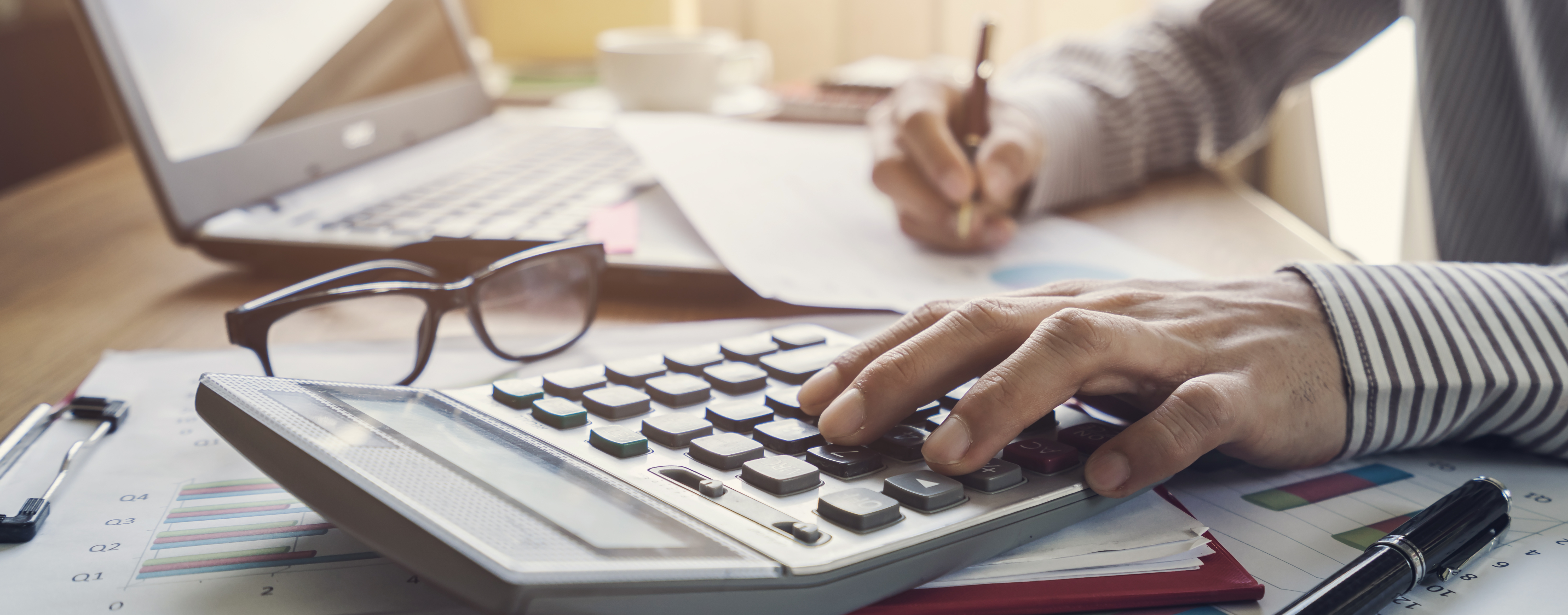 Man's hands typing on calculator with financial documents, glasses and a laptop on the desk.