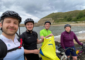 The team during the ride in front of the sea and hills, holding up a Tom's Trust vest.