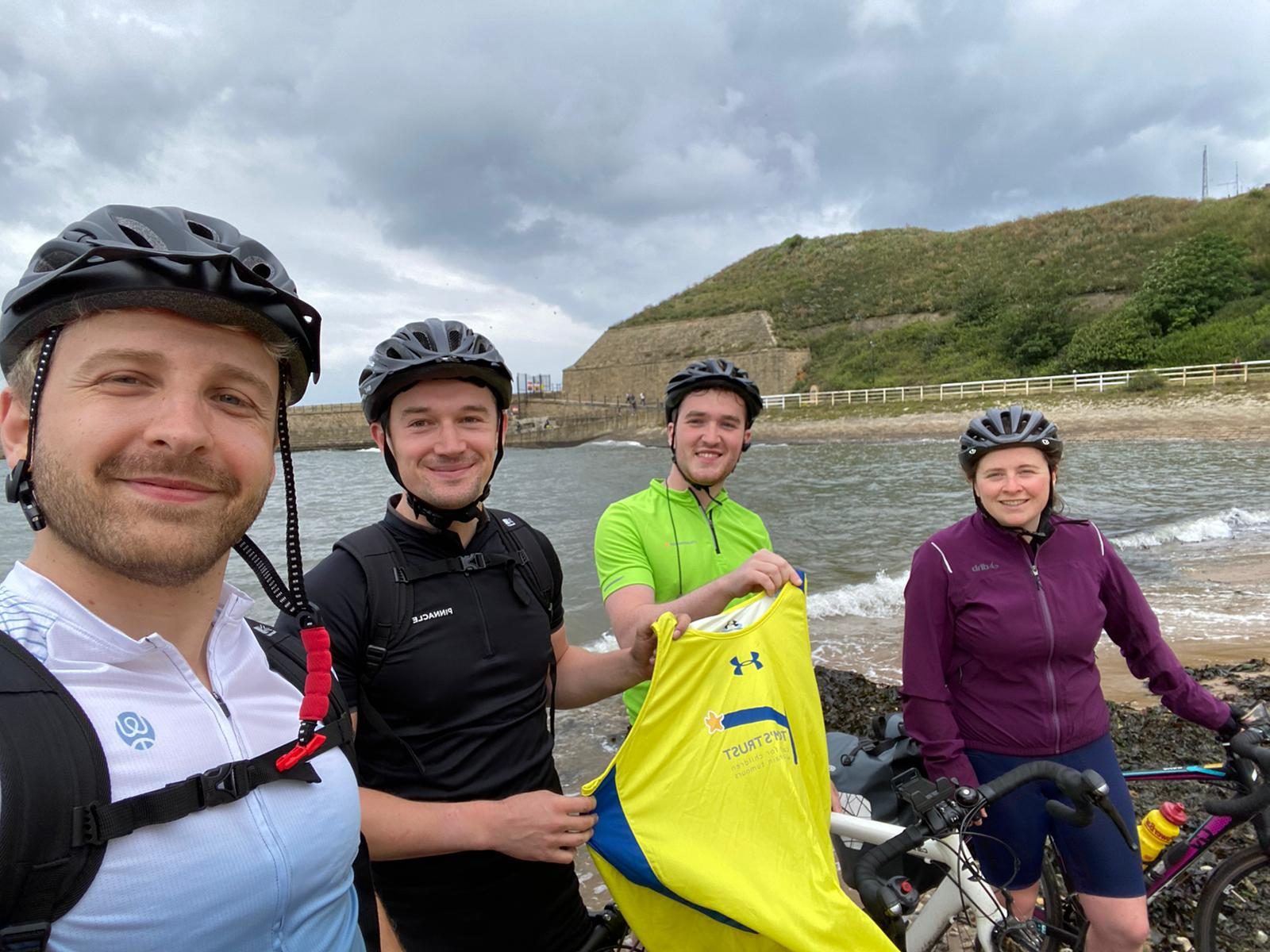 The team on their coast-to-coast challenge, standing in front of their bikes with helmets on, holding up a Tom's Trust vest. The background is the sea and hills.