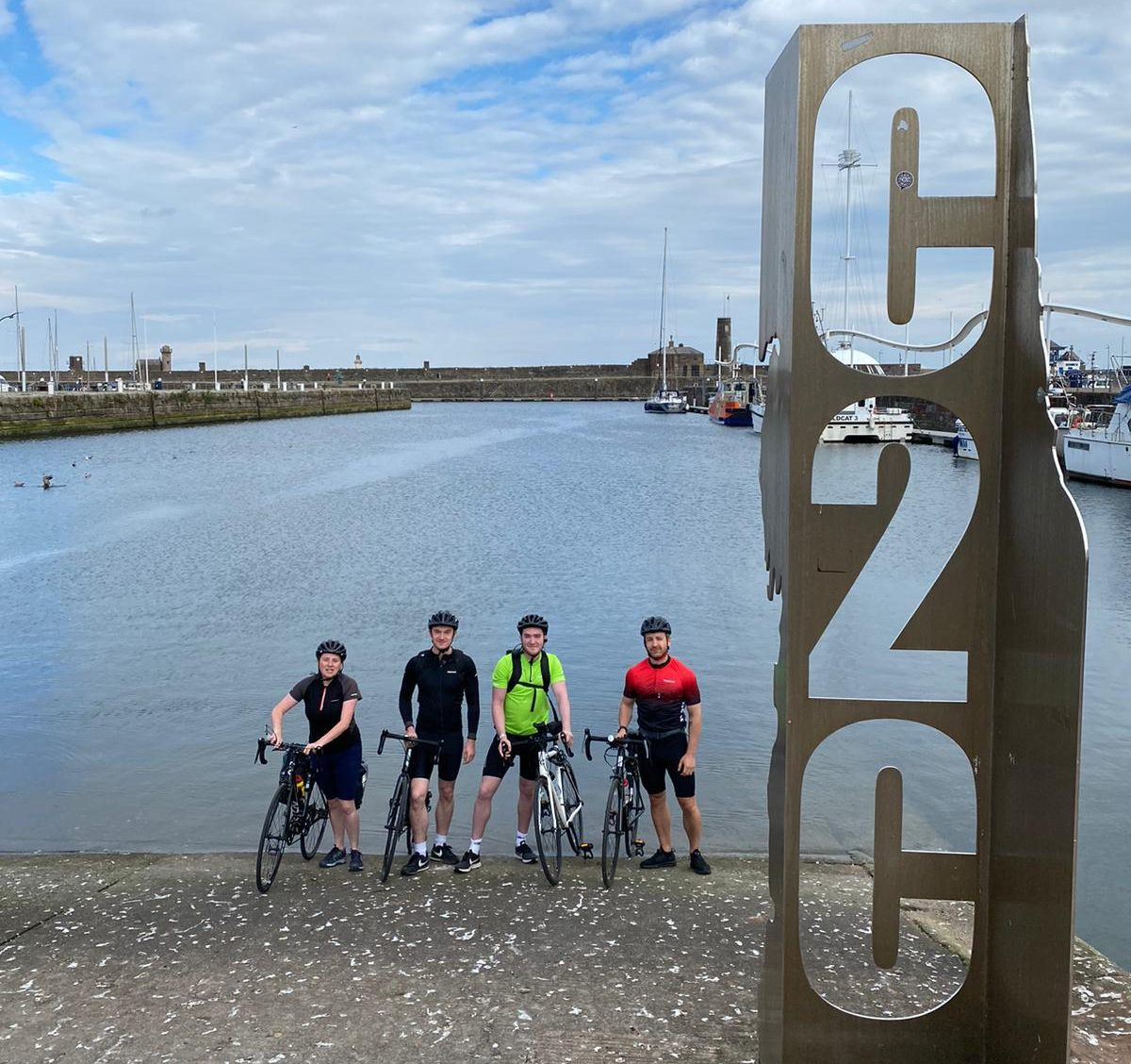 The team on their bikes in front of the sea.