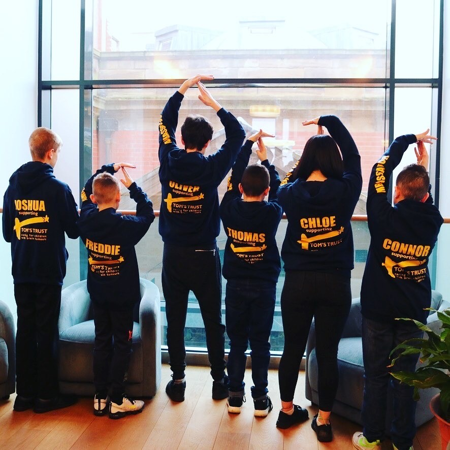 Young Ambassadors with backs turned showing of Tom's Trust hoodies.